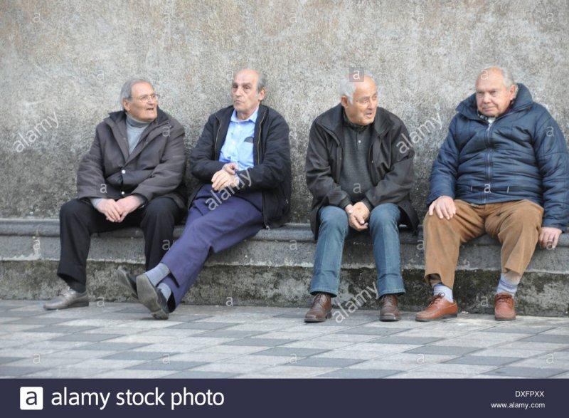 cuatro-hombres-ancianos-sentados-en-un-banco-conversando-y-pasando-la-hora-del-dia-dxfpxx.jpg